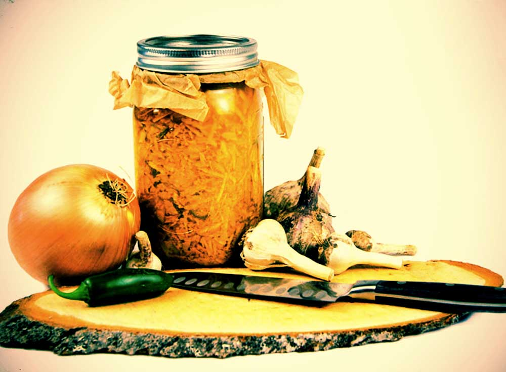 A knife, onion, jalepeno pepper and garlic sitting on top of a wooden, artisan looking cutting board next to a mason jar filled with materials on same cutting board