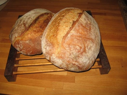 two oval shaped freshly baked bread loafs on a cooling rack with cutting board